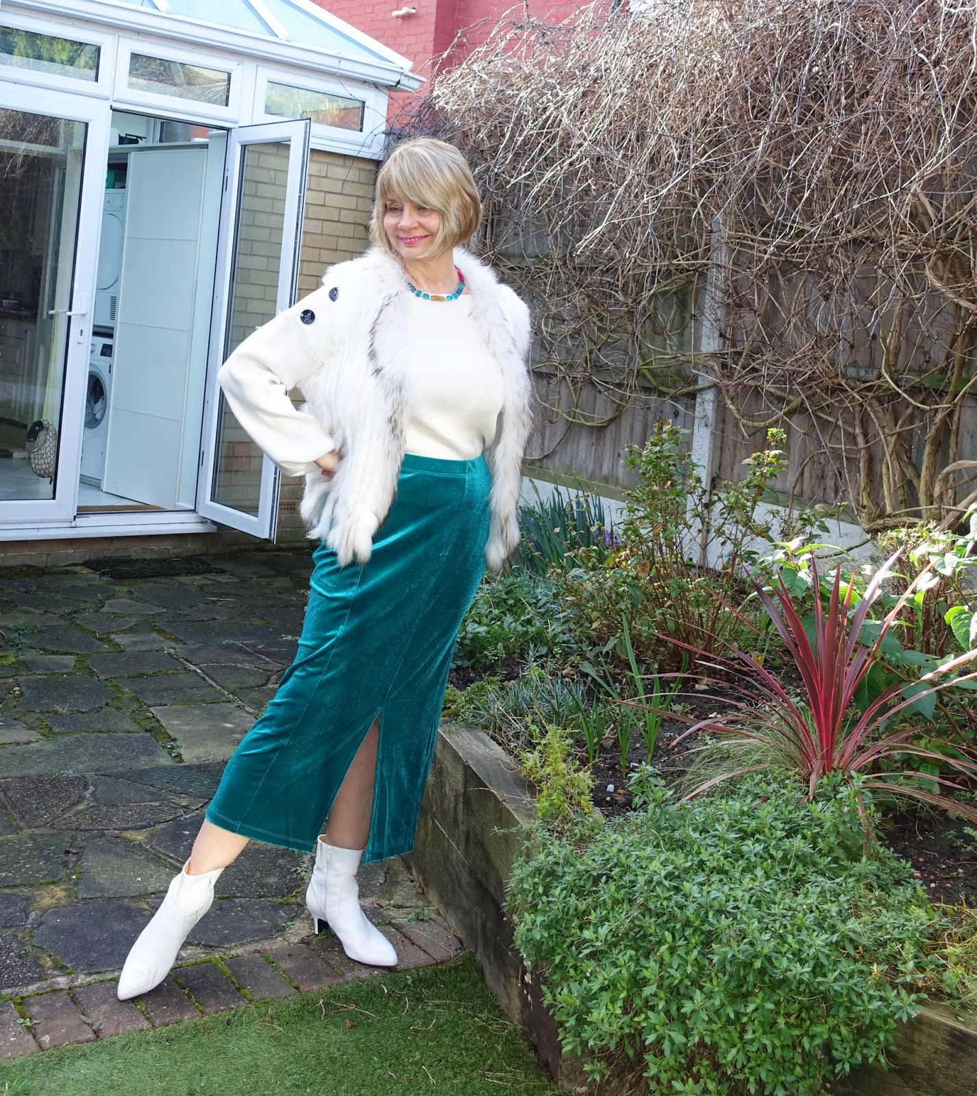 Teal velvet skirt worn with white boots, white jumper and furry gilet with a necklace by Corsi Design Factory