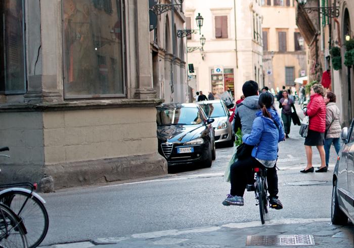 Un couple sur un vélo dans une ruelle de Florence, Italie.