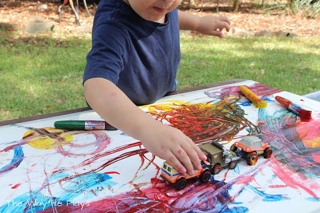 Toddler lining cars up in paint