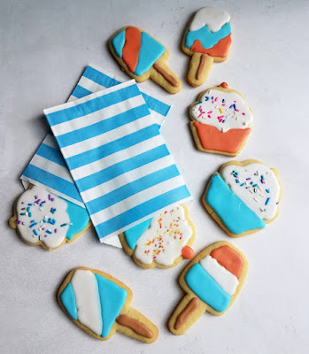 cupcake and popsicle sugar cookies with sprinkles in blue and white striped treat bags