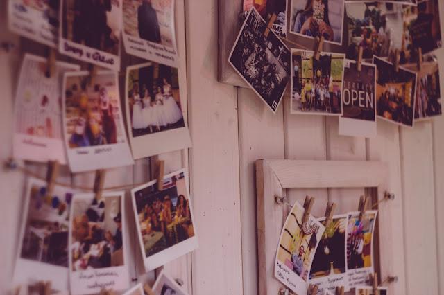 Polaroid photos hung up on a wall.