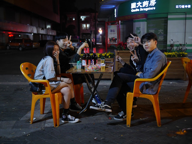 Four youth eating outside in Jiangmen