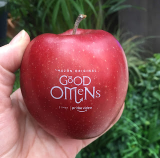 photo of a hand holding a red apple, on which appears the 'Good Omens' logo
