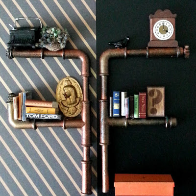 Two one-twelfth scale modern miniature pipe shelving units with different wallpaper behind them, and various books and objects on them.