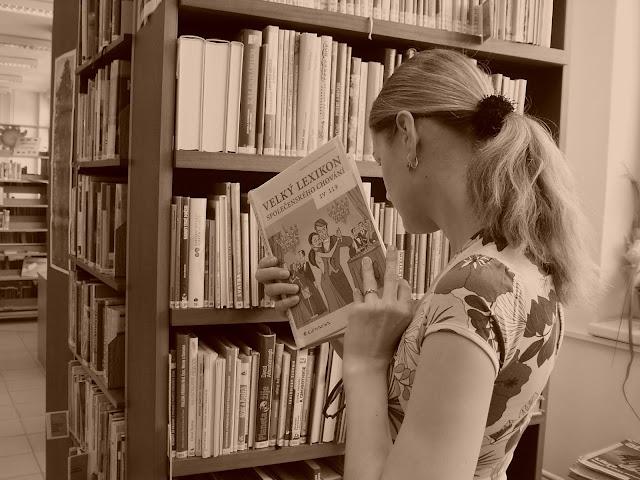 Linda prohlíží knihu v knihovně