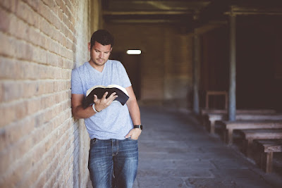 Man reading against brick wall