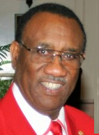 Photo of a middle-aged Black man with half-frame eyeglasses, wearing a red suit coat, red tie, and white shirt with red trim on the collar.