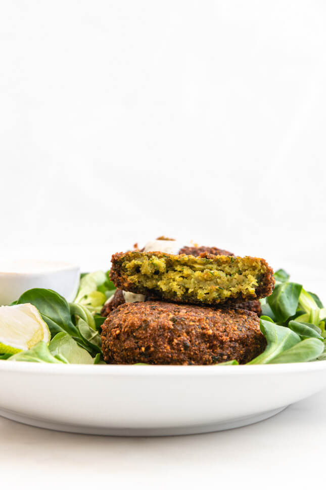 Profile photo of a plate with falafel decorated with vegetables and vegan yoghurt sauce