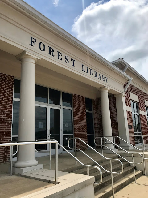 The outside of Forest Library, with large columns, metal handrails, and large glass doors
