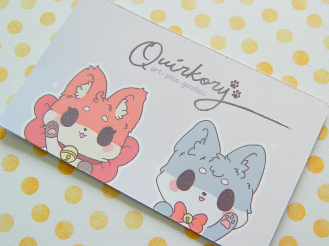 A photo showing a business card for Quirkory, featuring two mascots, a fox called Inari and a wolf called Mosted