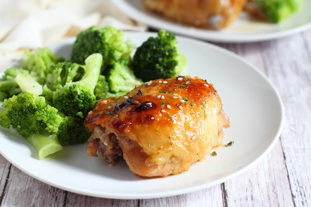 chicken thigh and broccoli on a white plate.