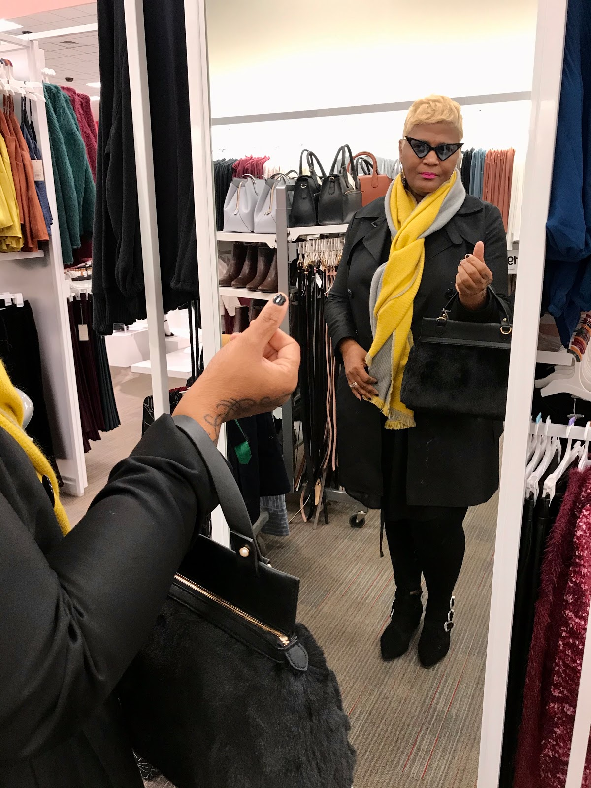 Tangie Bell trying on yellow scarf and faux fur handbag.