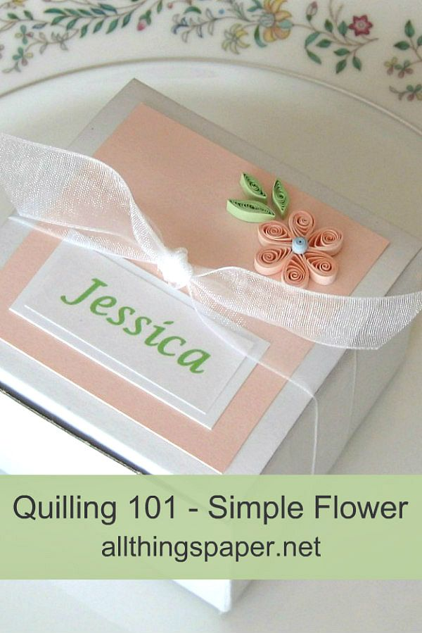 peach color six petal quilled flower with three quilled green leaves adorn a square favor box tied with white organdy ribbon