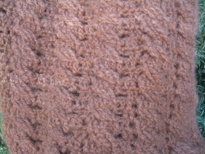 Close-up of the hood's cabled fabric.  There are streaks of lighter brown amidst the darker. This is the nature of undyed yarn.