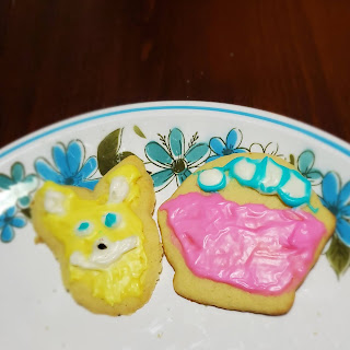 Two cookies sit on a white plate with a blue and green floral border. The left cookie is a deranged rabbit head with yellow fur. The right cookie is a pink Easter basket with white eggs outlined in blue.
