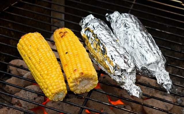 naked corn and corn on the cob in foil on the barbecue
