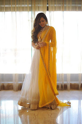 Indian Model Girl In White Yellow And Gold Lehenga And Dupatta. The look is completed with a statement of wavy hair and necklace.