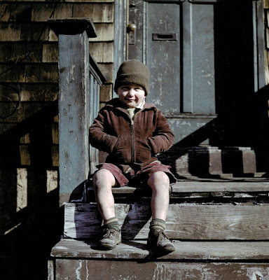 1947 color photograph of boy on steps with hand in pockets