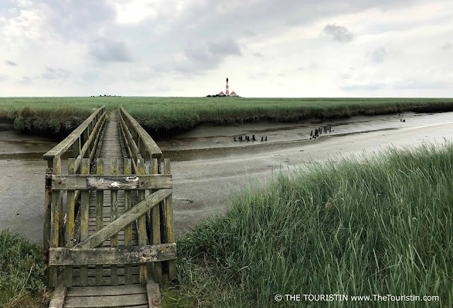 Wooden bridge over a creek in the wadden sea leading to a red and white lighthouse.