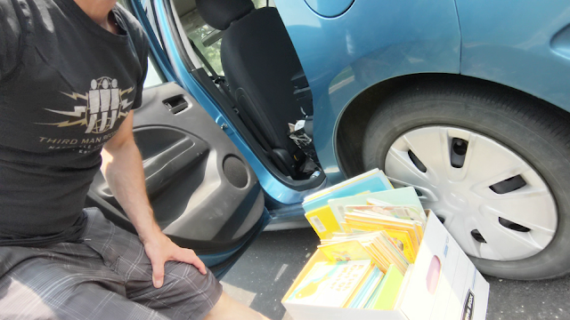 picture of guy with box of books next to a car