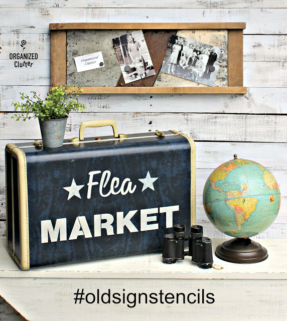 Photo of a stenciled suitcase, globe, binoculars, and slaw cutter photo display