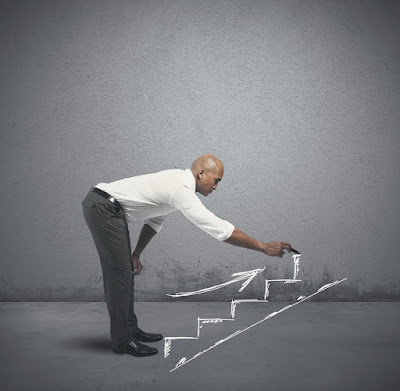 A man is drawing steps leading upward