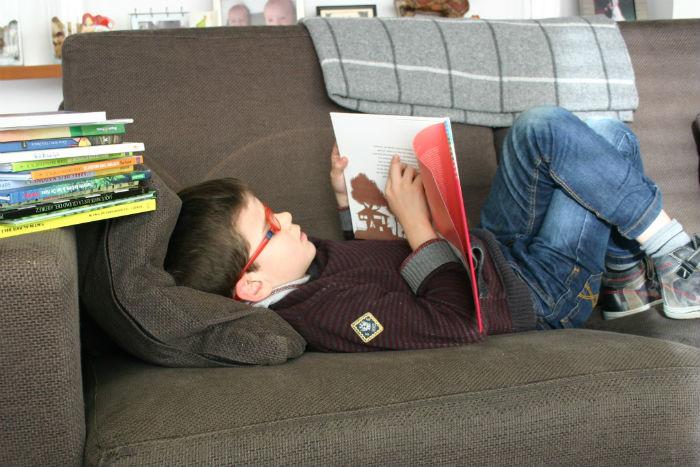 niño leyendo en sofá, con buena organización visual para poder seguir la línea del texto sin saltos ni repeticiones