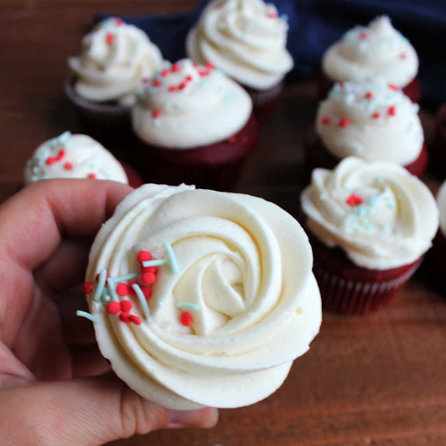 hand holding red velvet cupcake with ermine frosting rosette piped on top