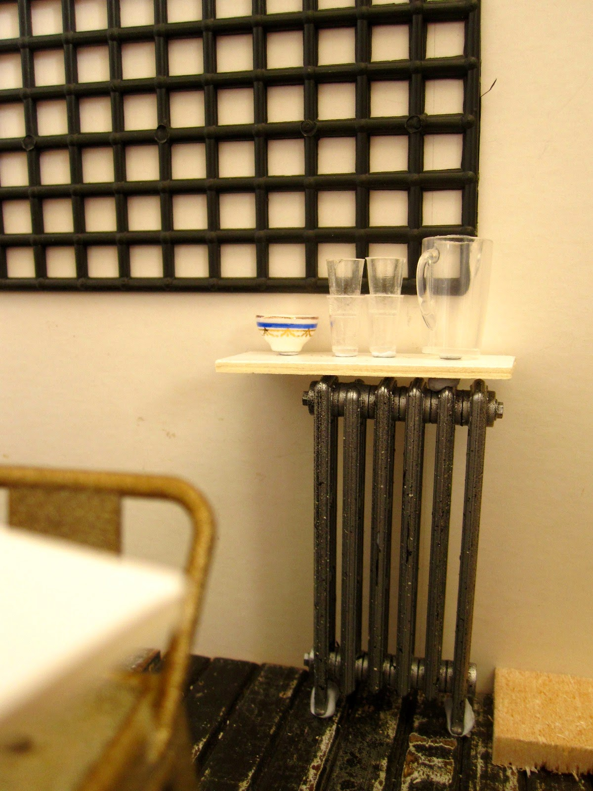 Modern dolls' house miniature half-built cafe, showing a radiator with a shelf on it, holding a water jug, glasses and a sugar bowl.