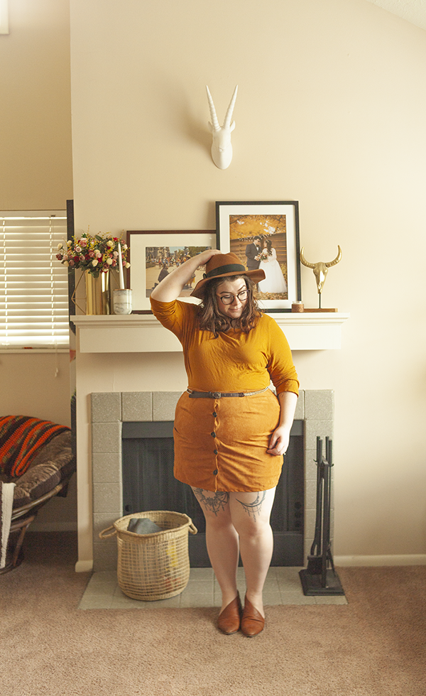 An outfit consisting of a brown panama hat, yellow brown top tucked into a brown button down mini skirt, and brown d'orsay flats.