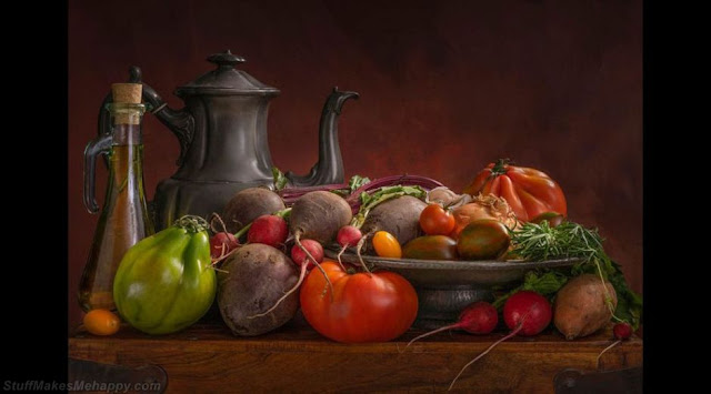 A still life combining fresh seasonal vegetables with rustic vessels and a massive wooden cutting board