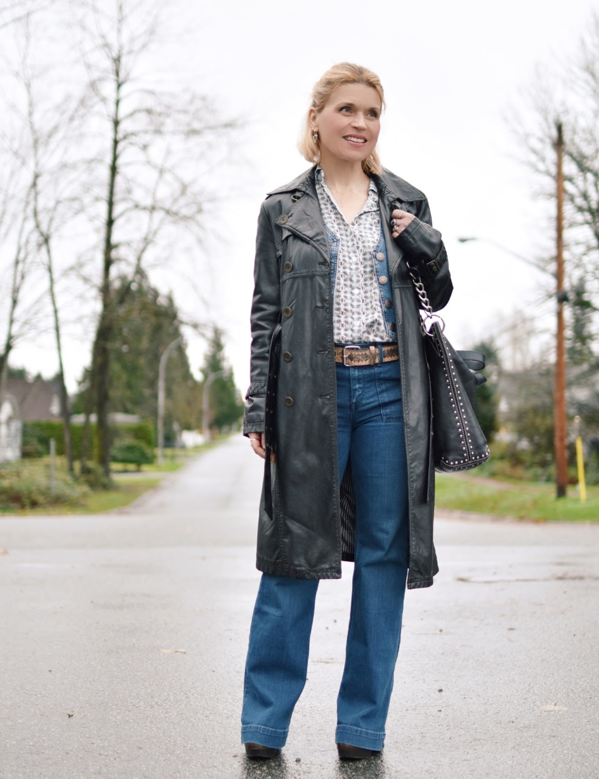 Monika Faulkner outfit inspiration - styling a faux-leather trench with a denim vest, patterned shirt, and flare jeans
