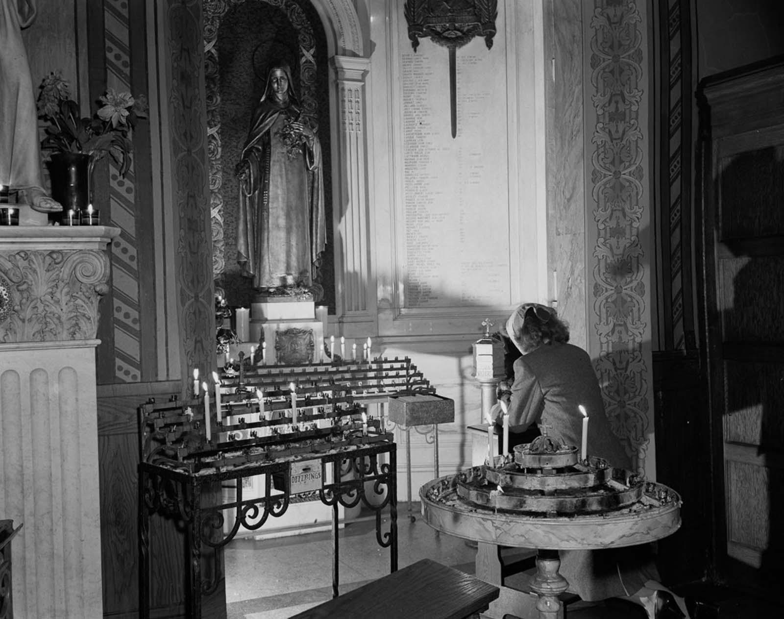A woman prays at St. Vincent de Paul's church on 23rd Street.