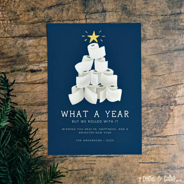 navy blue holiday card with toilet paper roll tree displayed on wooden background with greenery