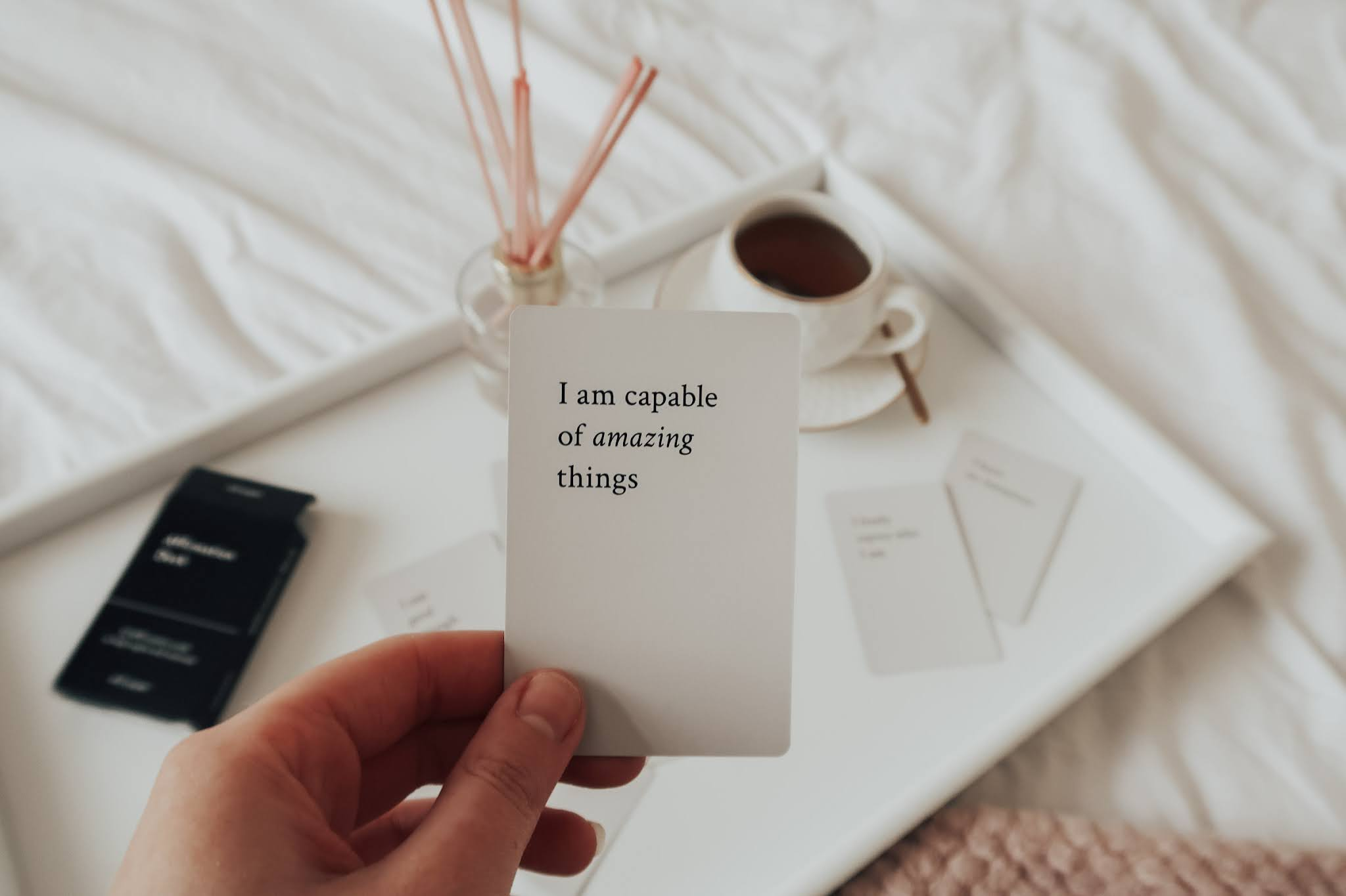 """Holding a white affirmation card with """"I'm Capable Of Amazing Things"""" written in black writing."""