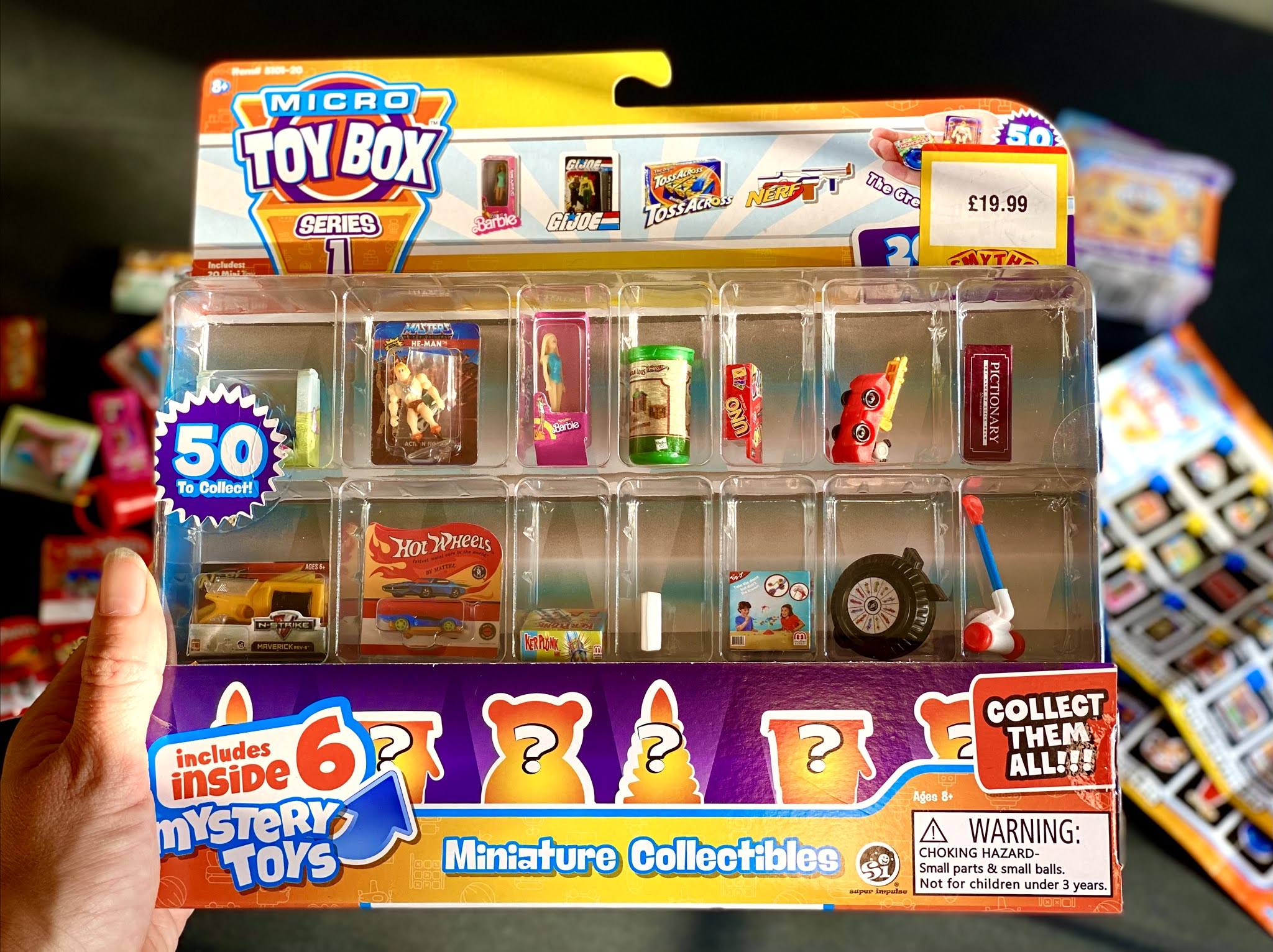 A 20 pack of Micro Toy Box collectibles being held
