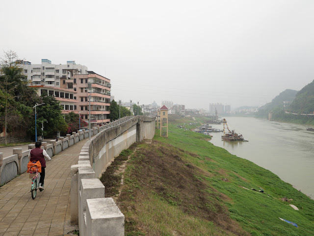 woman riding a bicycle on a wall bordering the Gui River (桂江) in Wuzhou (梧州)