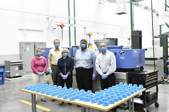 SLCC President Deneece G. Huftalin and cabinet members with dozens of masks produced by the injection molding machine behind them.