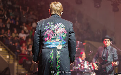 Elton John acknowledges fans behind the stage. Image of Elton John with embroidered pink Flamingos on back panel of his jacket.