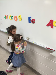 Young girl with long brown hair pulled up, white colored stripped shirt, jean skirt and a young girl with long brown hair, white shirt and black pants standing at a dry erase board working with magnetic letters