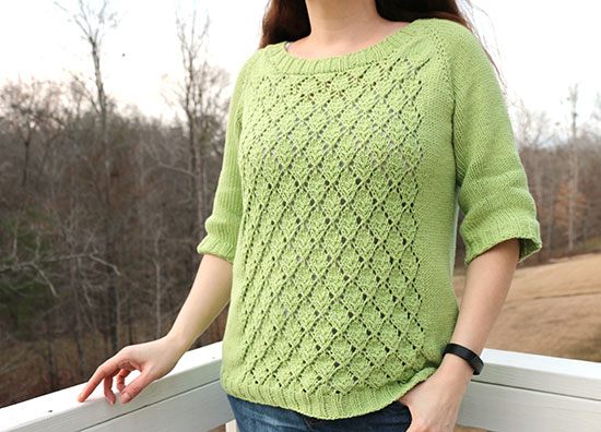 Close-up of woman standing in front of a white porch rail wearing a hand-knit spring green lace sweater, with leafless trees in the background.