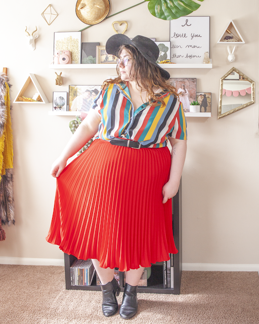 An outfit consisting of a black wide brim hat, a teal, red, white, black, light blue, and yellow vertical stripe short sleeve button up blouse unbuttoned tucked into a red pleated skirt and black chelsea boots.