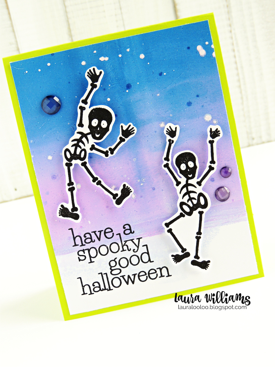 """Handmade Halloween card with a blue and purple background, printed on the Gel Press, with two rubber stamped and fussy cut skeletons. Sentiment says """"Have a Spooky Good Halloween""""."""