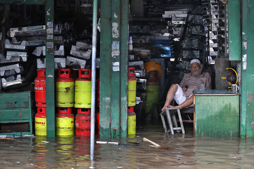 18 Devastating Pictures Of The Flooding In South Asia That Will Shock You - A Bangladeshi Man Sits In His Flooded Shop After Heavy Rain In Dhaka