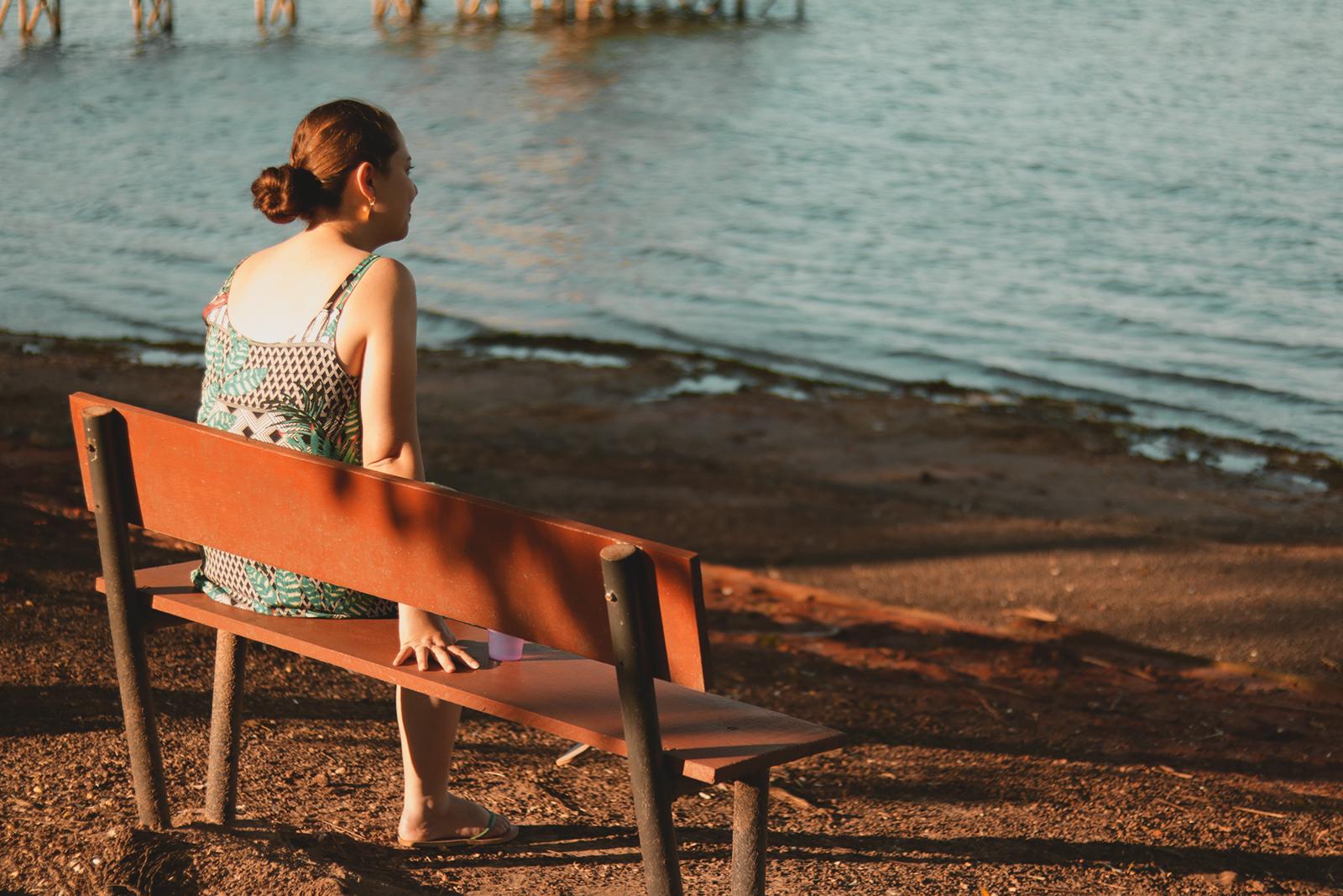 mulher sentada observando a água