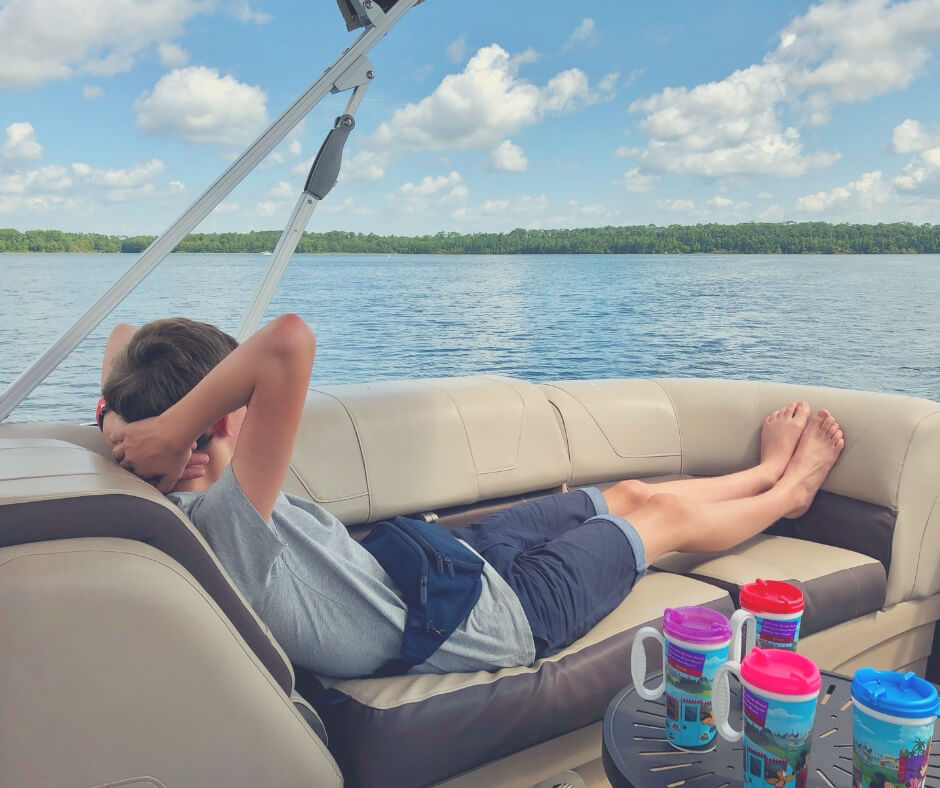 A teenage boy relaxes on a boat on Lake Buena Vista in Walt Disney World.