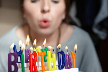 Blurred focus of a caucasian woman in the background in the foreground is lit candles shaped like letters spelling birthday the woman in the background is posed to blow the candles out