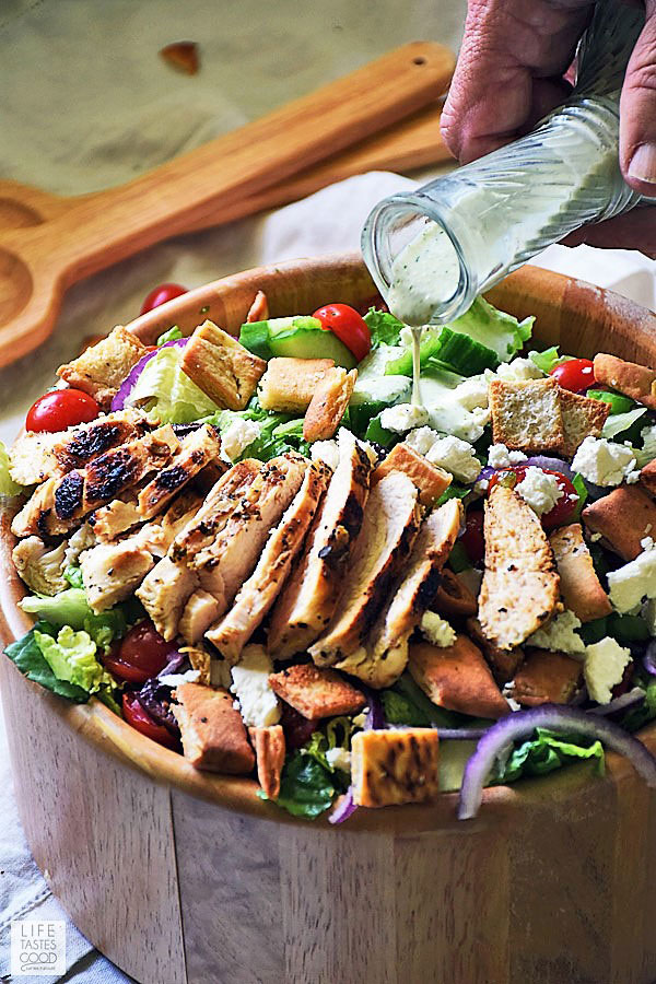 Gyros salad with chicken in a large wooden serving bowl drizzling on tzatziki dressing