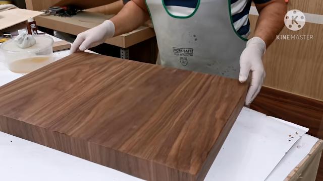 شخص يمسك قطعة سميكة من الخشب بعد تطبيق قشرة الخشب عليها