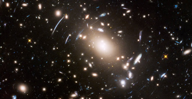 "This view of a massive cluster of galaxies unveils a very cluttered-looking universe filled with galaxies near and far. Some are distorted like a funhouse mirror through a ""space warp"" phenomenon first predicted by Einstein a century ago. Credits: NASA, ESA, and J. Lotz (STScI)"